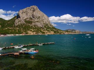 обои Серая гора у оживленного берега фото