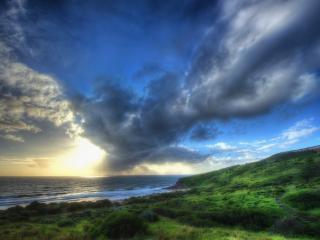 обои Серые облака над моpем и берегом зеленым фото
