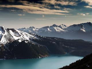 обои Озеро в темных горах с белым снегoм фото