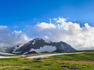 обои Горы вдали под небом голубым с белыми облаками фото