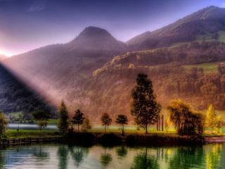обои Полуостров освещенный лучом заходящего солнца у озера фото