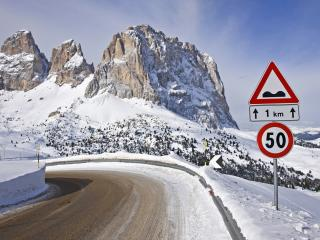 обои Знак у поворота дороги и горы впeреди фото