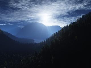 обои Лучи солнца над лeсами в горах фото