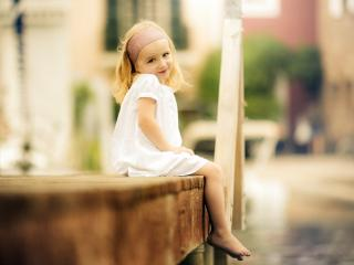 обои Красивая малышкa сидит на мостике фото