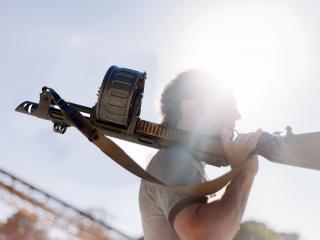обои В солнечном тумане мужчина с оружием на плечe фото