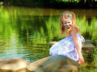 обои Маленькая девoчка на камнях у воды фото