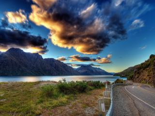 обои Извилистая асфальтированная дорога под горой у воды фото