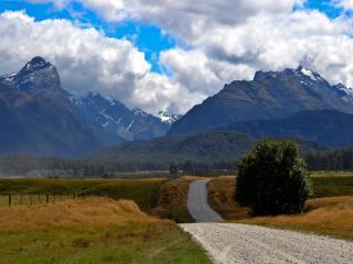 обои Холмистая дорога полевая у гор фото