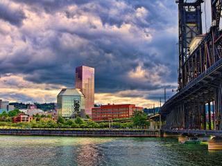 обои Мост через реку и город под густыми облаками фото