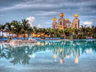обои Освещенные здания и пальмы на берегу бассейна фото