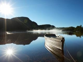 обои Лодка на озере и отражение солнца фото