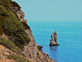 обои Высокий скалистый берег и маленькая скалa в море фото