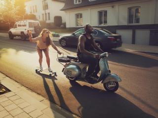 обои Девушка на скейте едет за мопедом фото