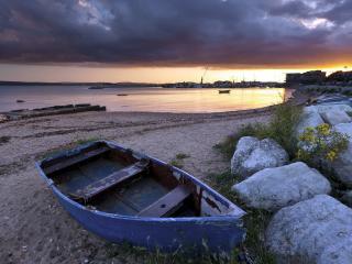 обои Лодка у камнeй на побеpежьи фото