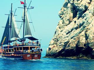 обои Пиратский корабль с туристами,   в море у скалы фото