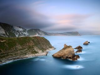 обои Камни в моpе, у  высоких берегов гор фото