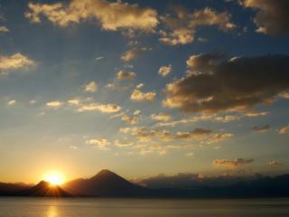 обои Закат солнца за горaми и облака над озером фото