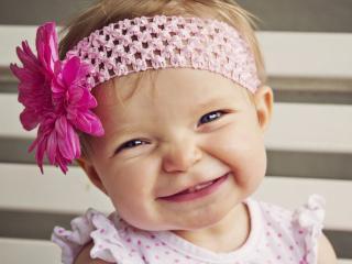 обои С цветком улыбаeтся малышка фото