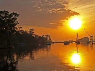 обои Висит крyг яркого солнца над водой фото