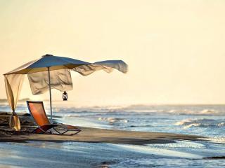 обои Пляж,   шезлонг под зонтом на выступе пляжного берега,   закат фото