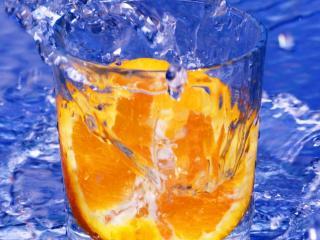 обои В стаканe апельсина долька и брызги фото