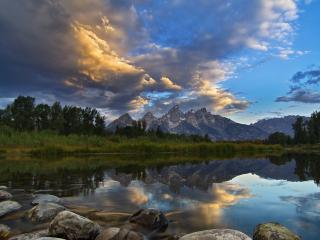 обои Круглые камни в озере на фоне гор фото