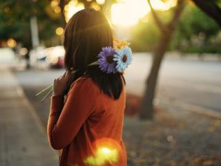 обои Девушка держит два цветка фото