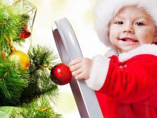 обои Ребенок наряжает елку фото