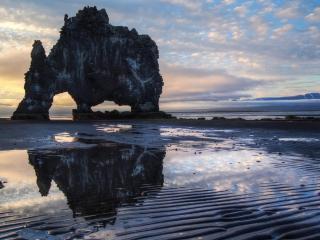 обои Скала с гротами на мелководье фото