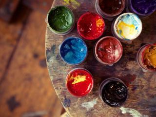 обои Краски в баночках на испачканом столе фото