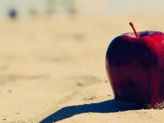 обои Красное яблоко в песке фото
