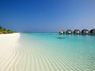 обои Одинокий пляж с шеренгой бунгал фото