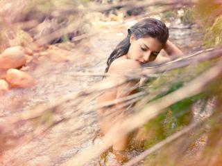 обои Брюнетка купается обнаженной в реке фото