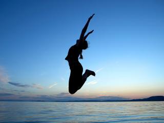 обои Девушка подпрыгнула на фоне моря фото