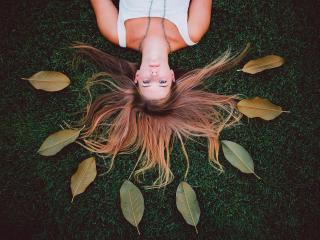 обои Девушка разложила волосы и листья на траве фото