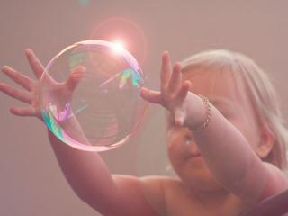 обои Ребёнок и огромный мыльный пузырь фото